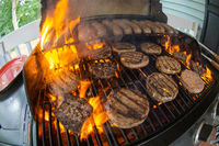 burgers and sausages cooking on grill