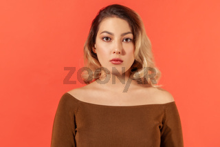 Emotional young woman on orange background.