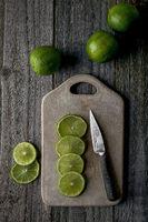 geschnittene Limettenscheiben auf Holzbrett