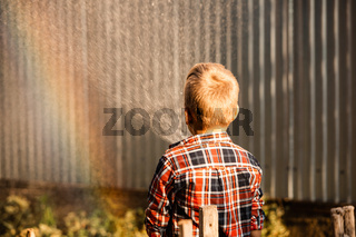 The boy enjoys a rainbow while watering in the garden
