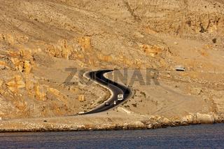 S-förmiger Ausschnitt der Küstenstrasse nach Khasab in den kahlen Berge am Ufer des Persischen Golfs