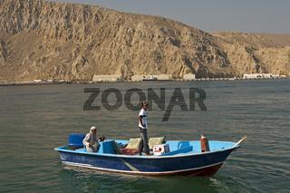 Motorboot mit zwei arabischen Männer vor der kahlen Felsenküste bei Khasab