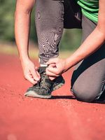 Woman is lacing shoe. Morning regular training and jogging