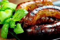Pork meat sausages on a black plate