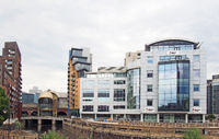 view of leeds with the river aire entering the dark arches under the railway station with pedestrian footbridge and office and apartment buildings