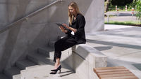 Female manager using tablet on steps