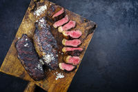 Traditional barbecue dry aged wagyu Brazilian picanha steaks from the sirloin cap of rump beef sliced and served as top view on a rustic wooden board with copy space right