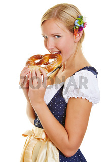 Frau im Dirndl beißt in Brezel