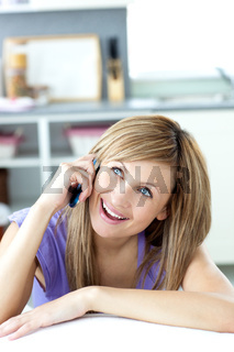 Caucasian woman talking on the phone in the kitchen