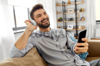man in headphones listening to music on smartphone