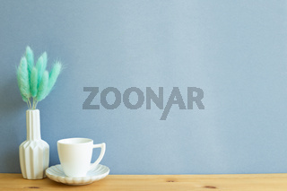 Coffee cup with vase of Lagurus ovatus dry grass on wooden table. Blue background, copy space