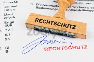 Holzstempel auf Dokument: Rechtschutz