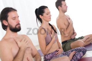 Group of young sporty attractive people practicing yoga lesson with instructor in modern bright yoga studio.