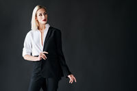 Young stylish woman wearing classic men's suit posing on black studio background with copy space