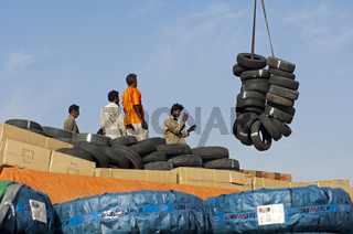 Hafenarbeiter dirigieren eine Kranladung von gebrauchten Fahrzeugreifen im Hafen von Dubai