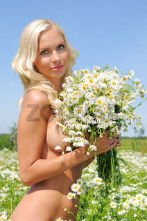 naked woman at the meadow with bunch of  chamomiles.