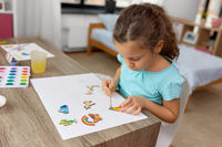 little girl painting wooden items at home