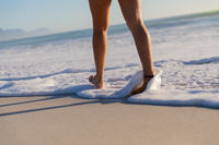Caucasian woman walking towards the sea at the beach