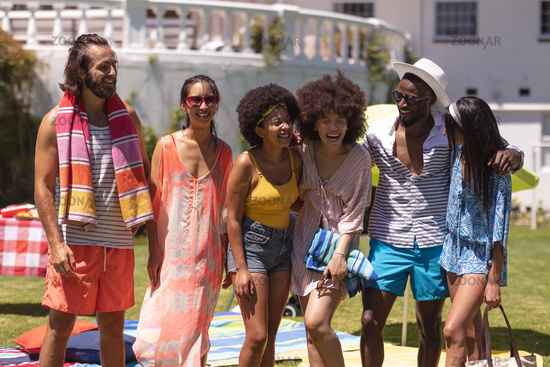 Diverse group of friends embracing and smiling at a pool party