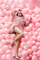 Top view of fashion pretty woman lying in many pink balloons