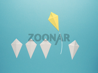 White paper kites in a row with a yellow paper kite flying away