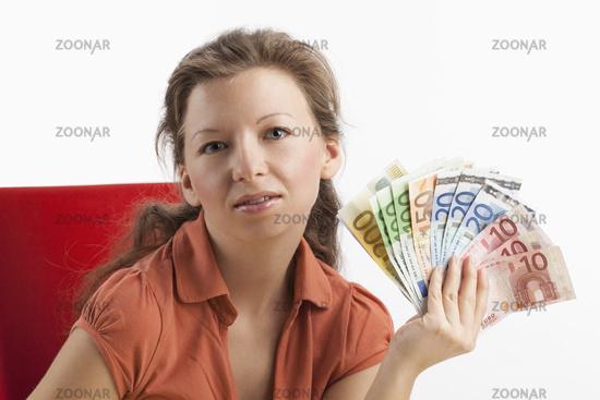 Frau mit Fächer aus Papiergeld in der Hand