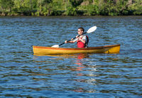 Male caucasian paddling a pack canoe with a kayak paddle on lake