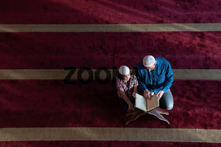 father and son reading holly book quran together islamic education concept