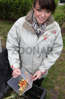 Woman composting vegetables