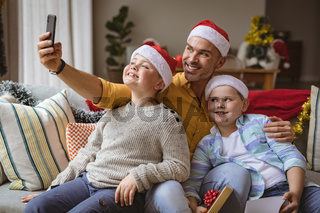 Caucasian father and two sons talking a selfie from smartphone at home during christmas