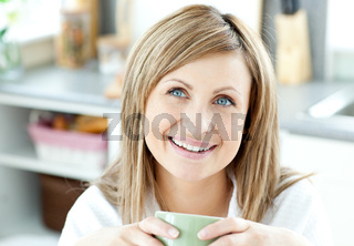 Happy woman holding a cup of coffee in the kitchen