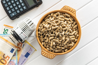 Ecological heating. Wooden pellets, euro banknotes, calculator and thermostatic head.