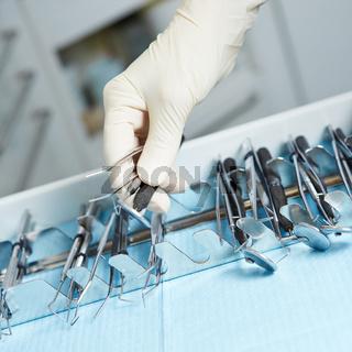 Zahnarzt greift mit Hand nach Werkzeugen