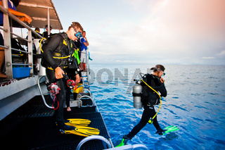Diver stepping off the boat into the ocean