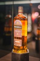 Rare, aged 21 year Bushmills whiskey on illuminated display in distillery shop