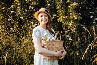 Pretty woman in hat holding basket with flowers