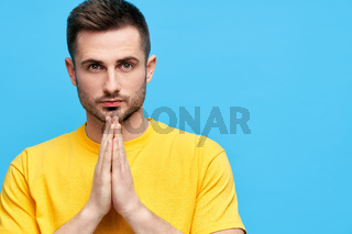 Portrait of handsome man with praying hands looking to camera with copy space