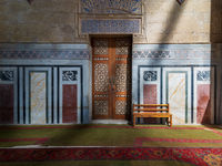 Ornamental wooden door, mosaic decorated walls, wooden bench, and floor lit by sunbeams, Al Rifai Mosque, Cairo, Egypt