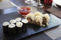 Japanese rolls sushi with cucumbers and shrimps fried on wooden black plate