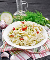 Fettuccine with zucchini and hot peppers in plate on black board