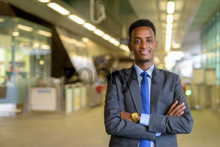 Portrait of handsome African businessman traveling in city
