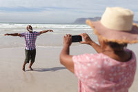 Senior african american woman taking a picture of her husband on the beach