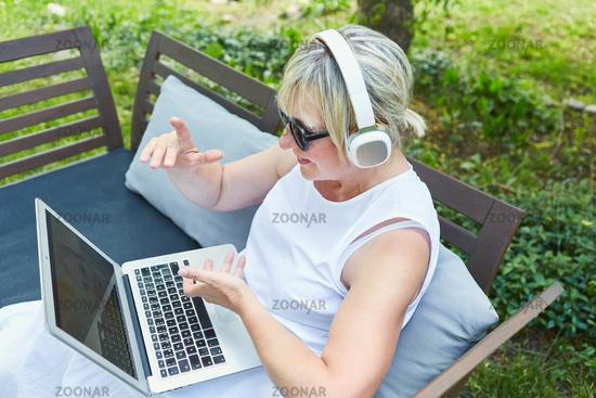 Frau als Freelancer am Laptop PC bei Videokonferenz