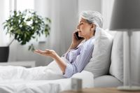 senior woman calling on smartphone in bed at home