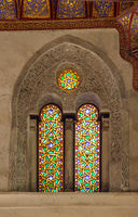 Two adjacent perforated stucco arched windows with colorful stain glass patterns, at Qalawun complex, Cairo, Egypt