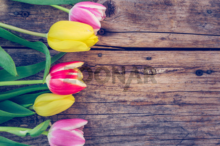 Arrangement of colorful tulips on a rustic wooden table, text space
