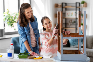 mother and daughter sanding old table with sponge