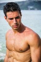 Handsome young man getting out of water with wet hair