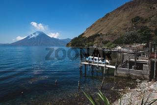 Coastal view with jetty along the village on lake Atitlan with view on volcano peak in Santa Cruz la Laguna, Guatemala