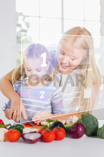 Mother and daughter chopping vegetables with holographic interface